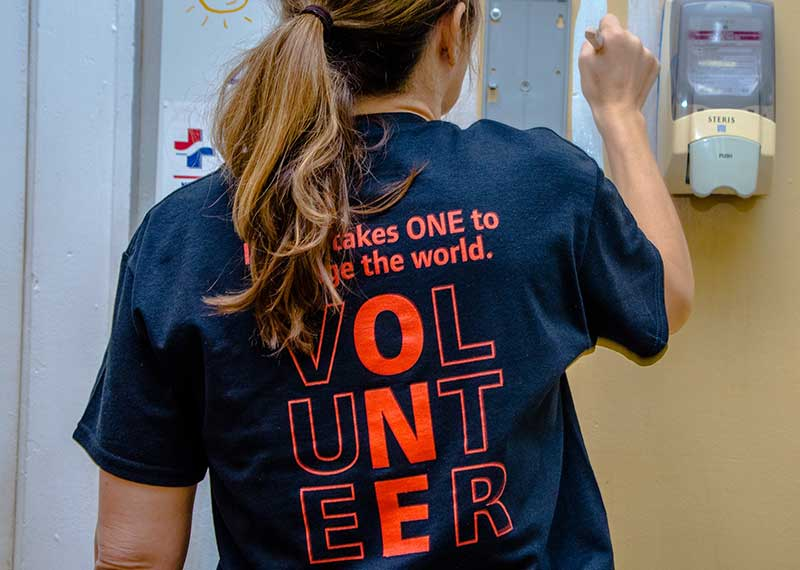 A woman Ingersoll Rand employee wearing a volunteer t-shirt paints a wall